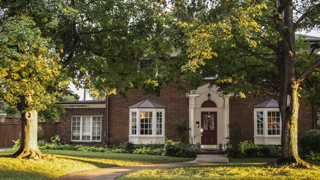 Golden Hour on the maple trees in front of traditional brick house with columns and bay windows - light stretching across front yard and up tree trunks