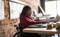 Businesswoman in wheelchair working at desk