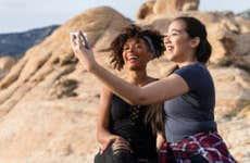 Two women taking a picture in a scenic nature landscape