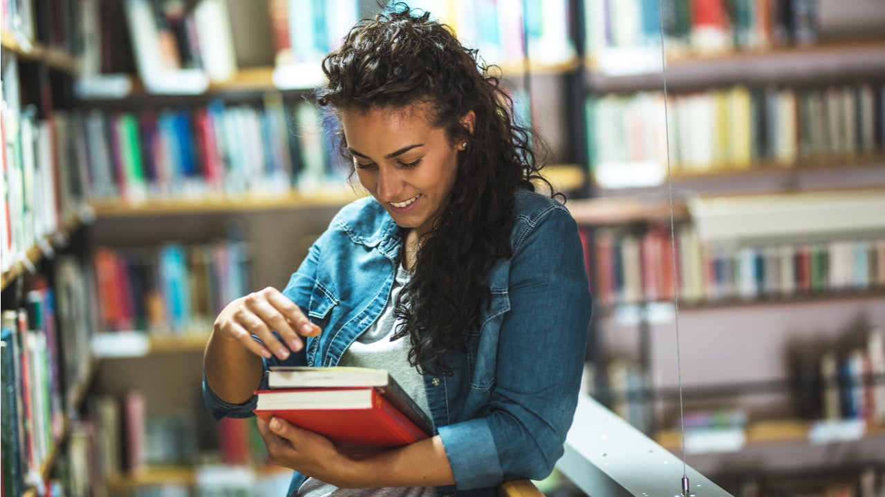 Woman checks out books in college library