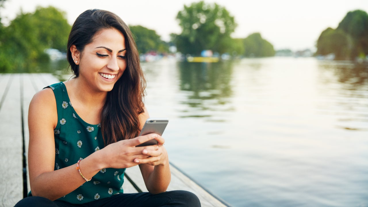 A young woman looks at her phone on a jetty