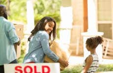 Black family moving into a new home. Mother, father and daughter. Real estate sign. Home in background. Spring or summer season.