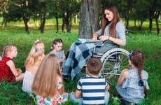Woman in wheelchair reads aloud to a group of kids
