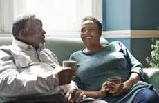 Smiling senior couple talking on sofa at home