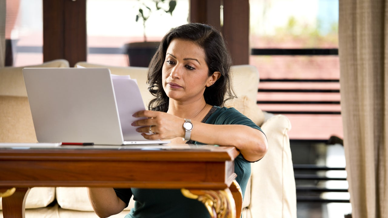 Frustrated woman reading document at home office