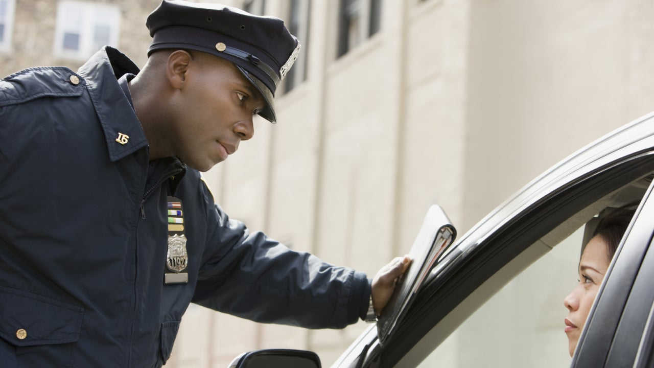 African policeman giving woman ticket