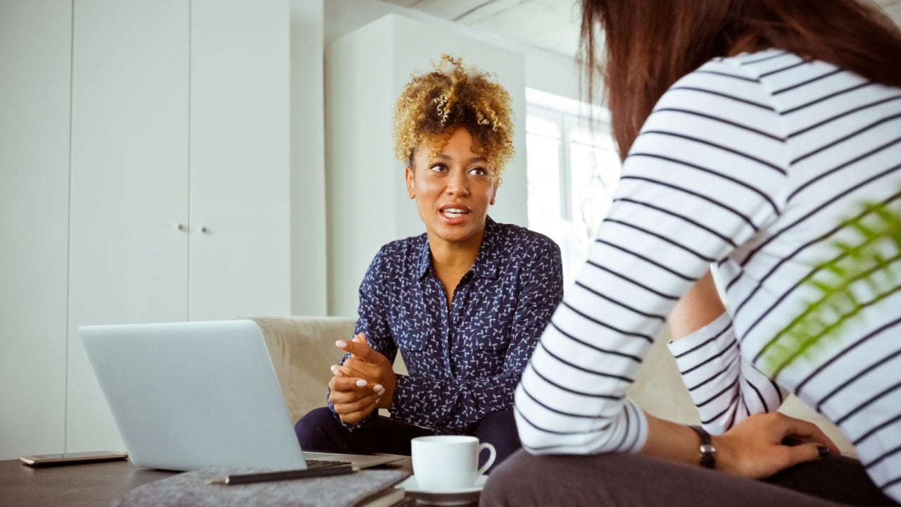 Mid adult businesswoman talking with customer