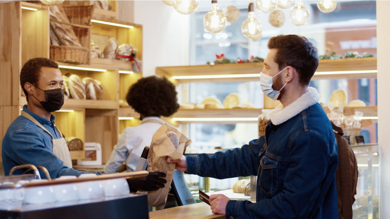 Masked customer making credit card purchase in bakery
