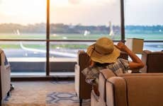 Female traveler with hat looking at airplane from modern airport lounge