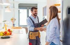 Young Woman Shaking Hands To Male Plumber With Clipboard In Kitchen