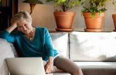 A senior woman works on a laptop.