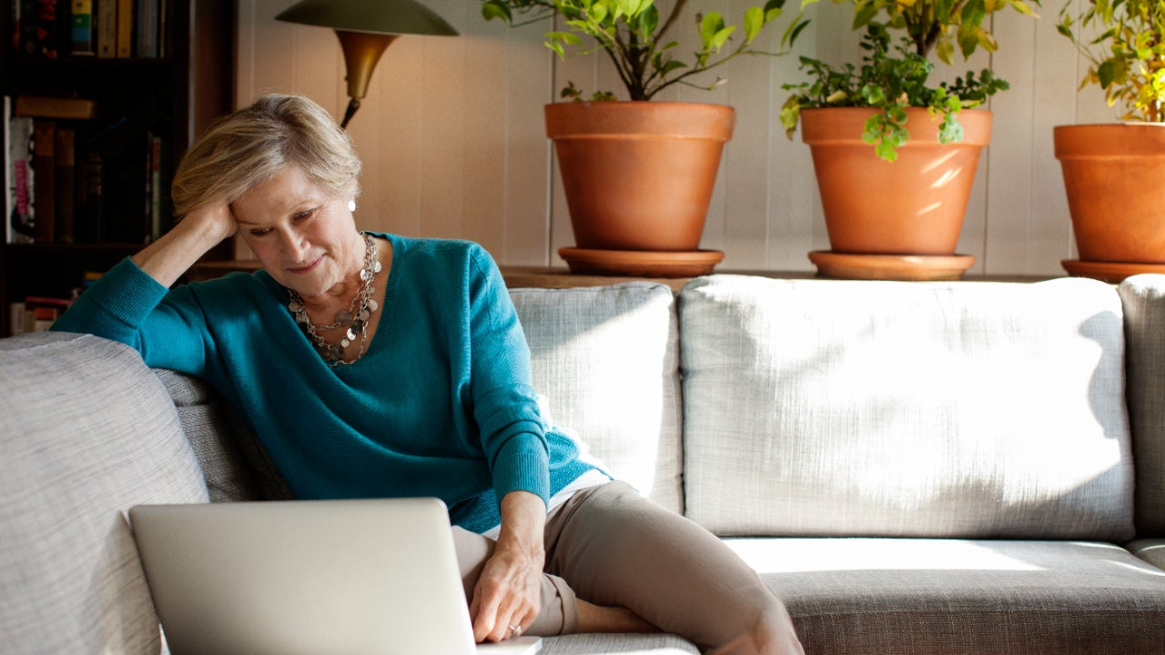 A senior woman works on a laptop.