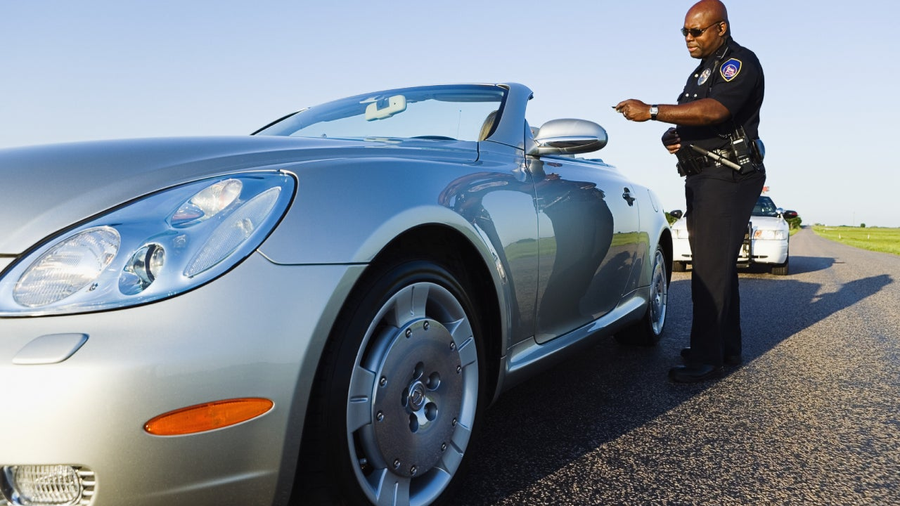 Police officer standing near a convertible car holding a driver's license