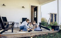Mother and sons playing checkers on front porch of home