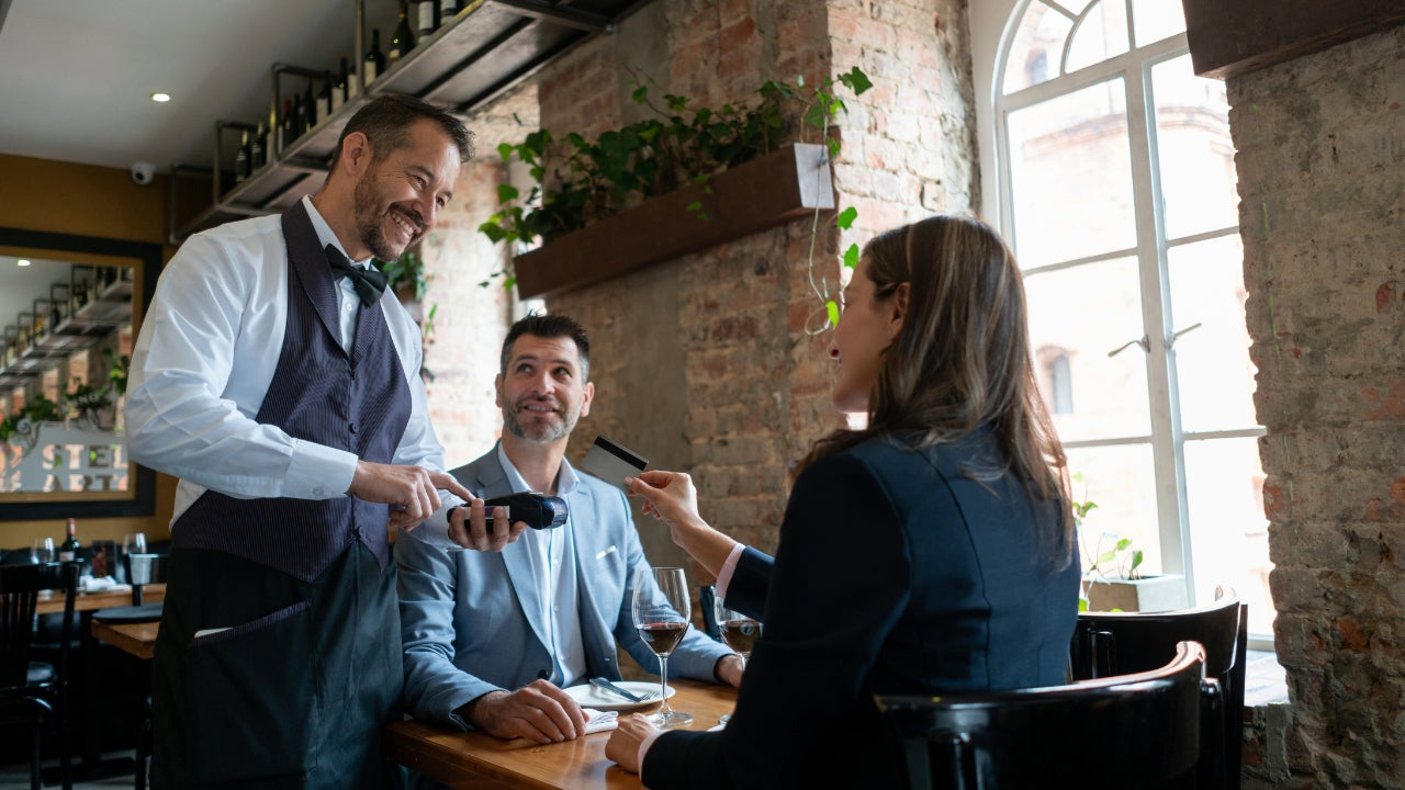 Woman dining at restaurant paying with credit card
