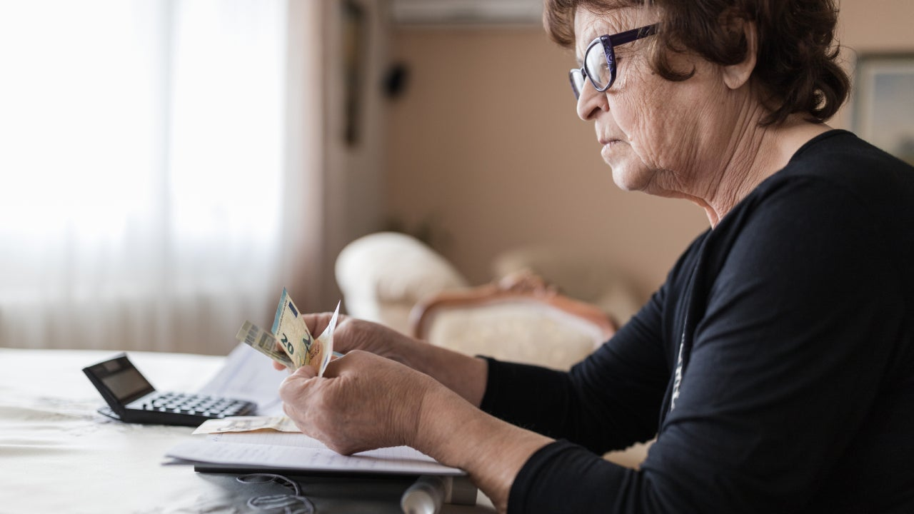 Senior woman holding money in her hands at home