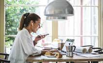 Smiling female entrepreneur using laptop while talking through smart phone at home office