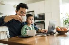 A father multi-tasks with his young son.