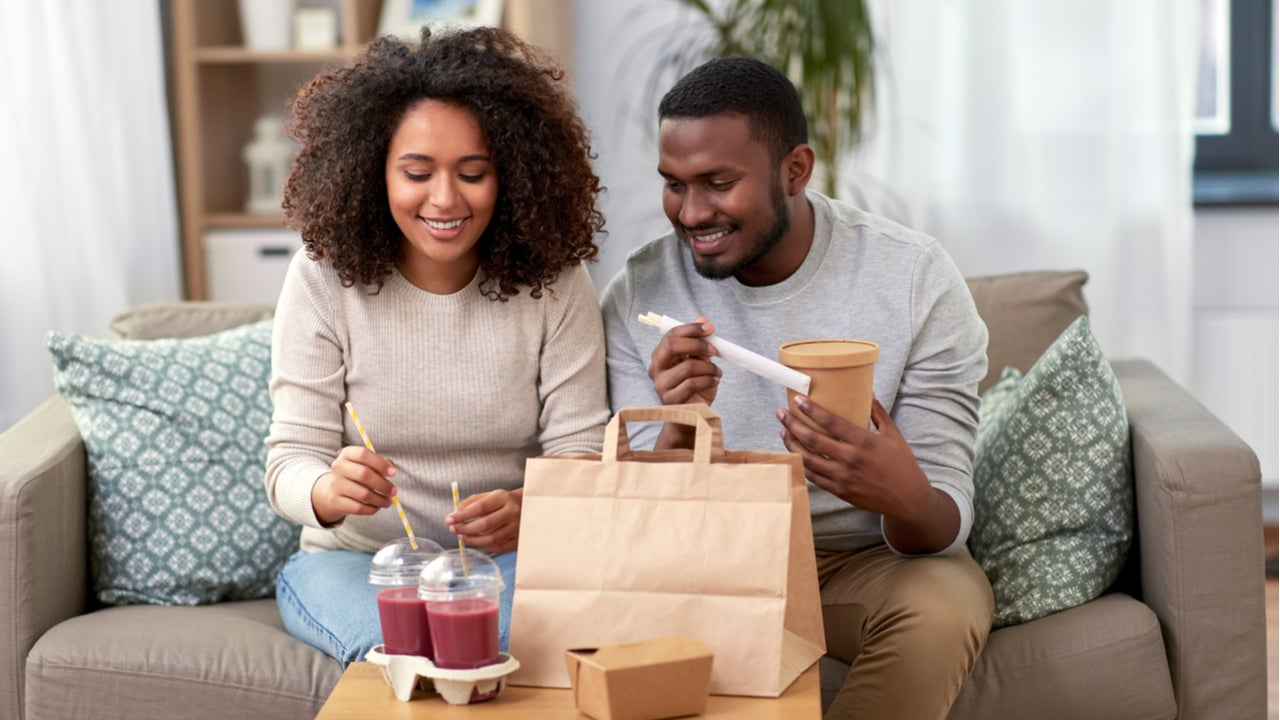 Black couple eating take out at home