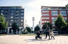 A father with two young children walking in front of condo buildings in the city