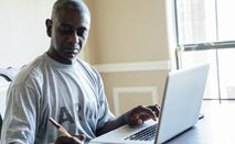 Black man using laptop and notebook at table