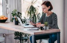 Woman working on laptop and smartphone