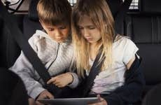Sibling using digital tablet while sitting in electric car
