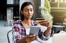 Young woman with credit card on her phone