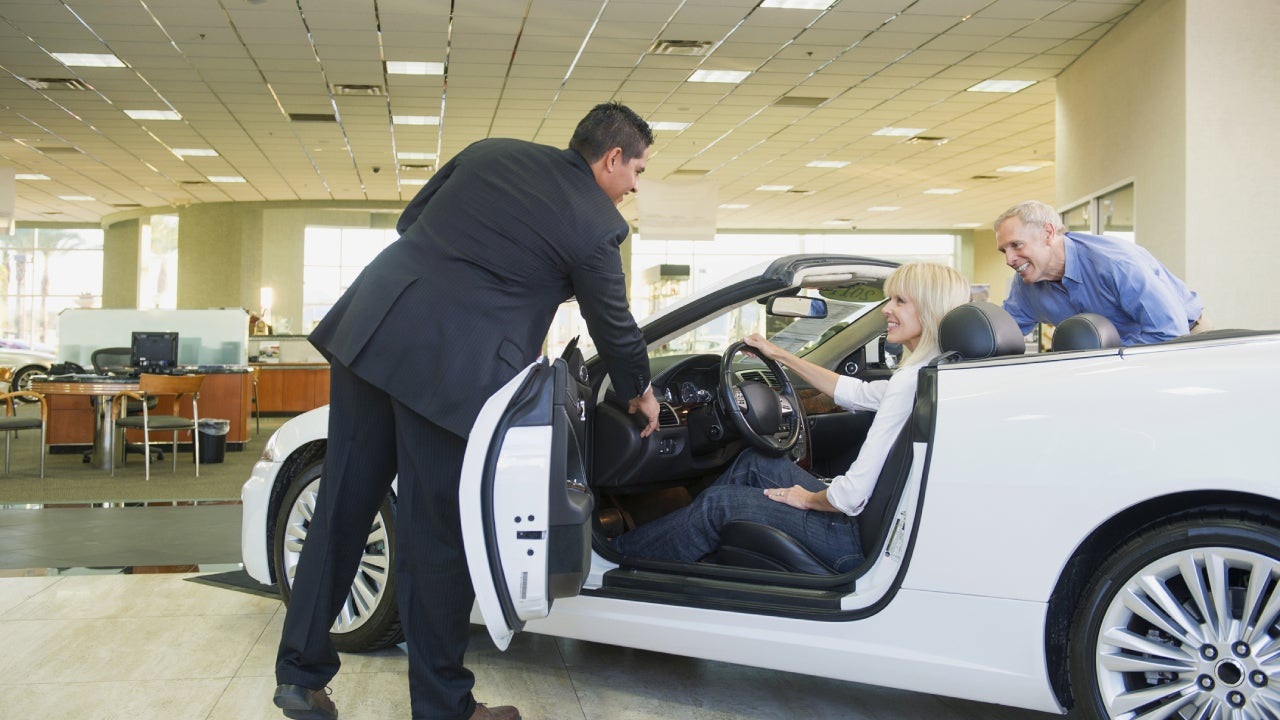 Salesman showing convertible to couple in car dealership