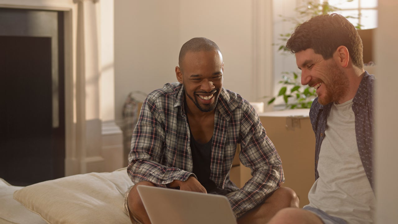 Two men in their new home looking at a laptop