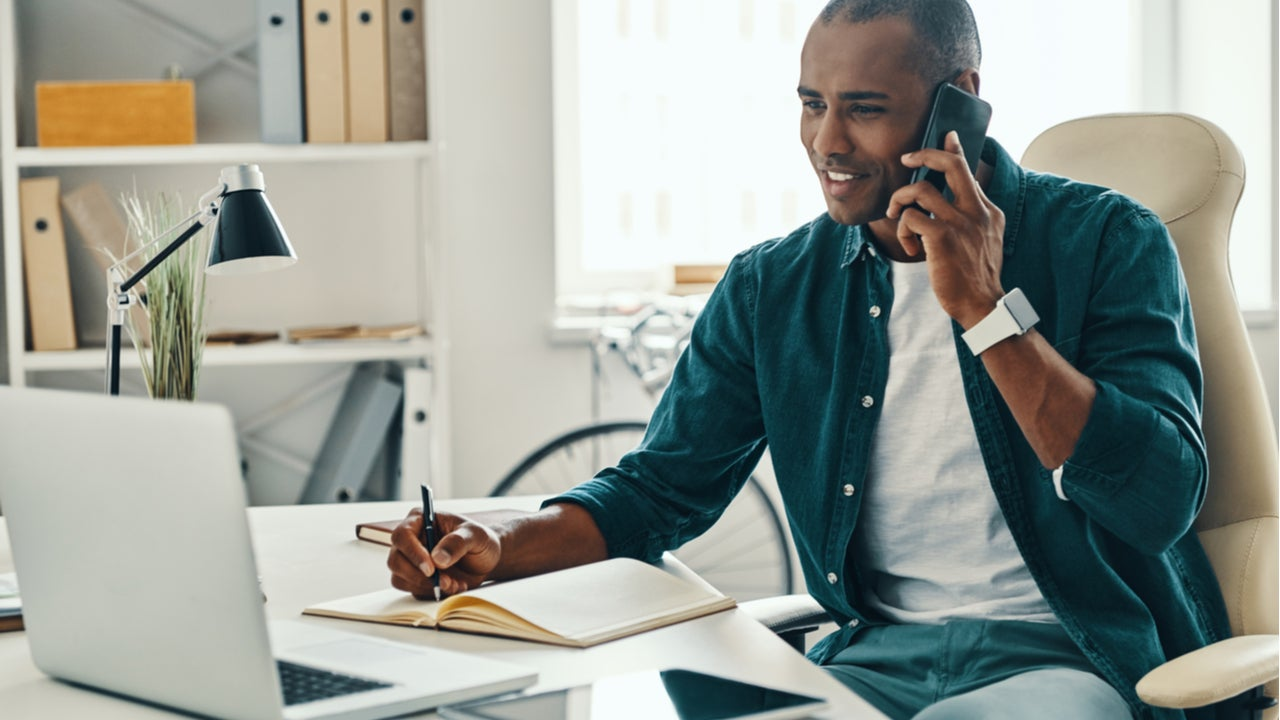 Young man working at modern desk on phone