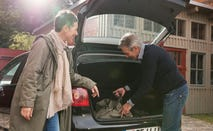 Married couple loading luggage into truck of car