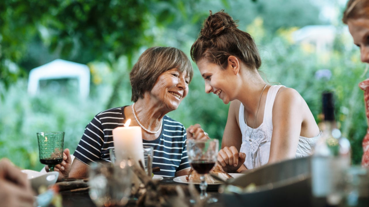 A younger daughter laughs with her older mother at a dining table