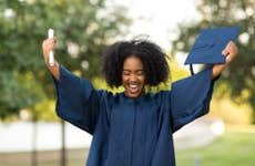 Woman holds up diploma at graduation
