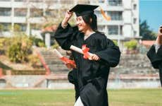 Woman carries diploma at graduation