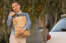 Delivery woman calling a customer after coming with their order
