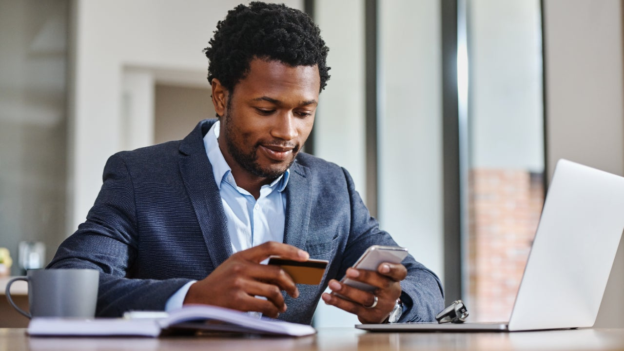 Business person holding credit card and phone