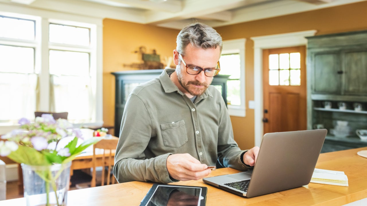 Person sitting at computer while holding a credit card