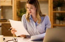 A woman sits at her dining room table with laptop and financial reports