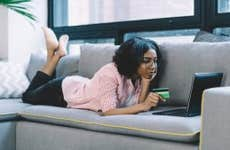 Black woman laying on couch using laptop and holding credit card