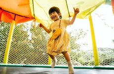 Joyful little Asian toddler girl smiling happily and having fun jumping in a bouncy castle in a outdoor playground