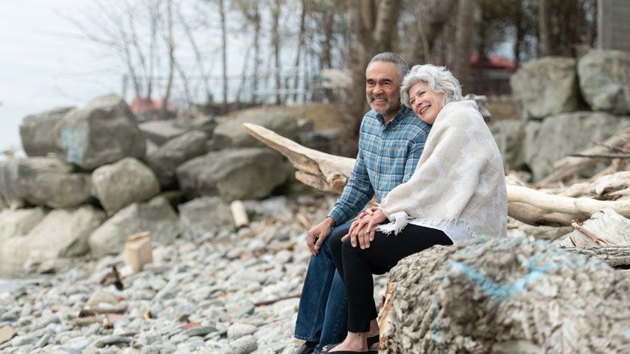 An older, interracial couple sits on a rocky shore and enjoys the view.