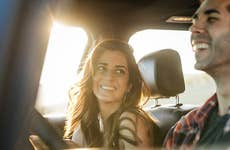 happy couple driving in car on road trip