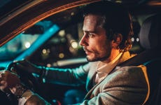 Gentleman driving a car in city at night