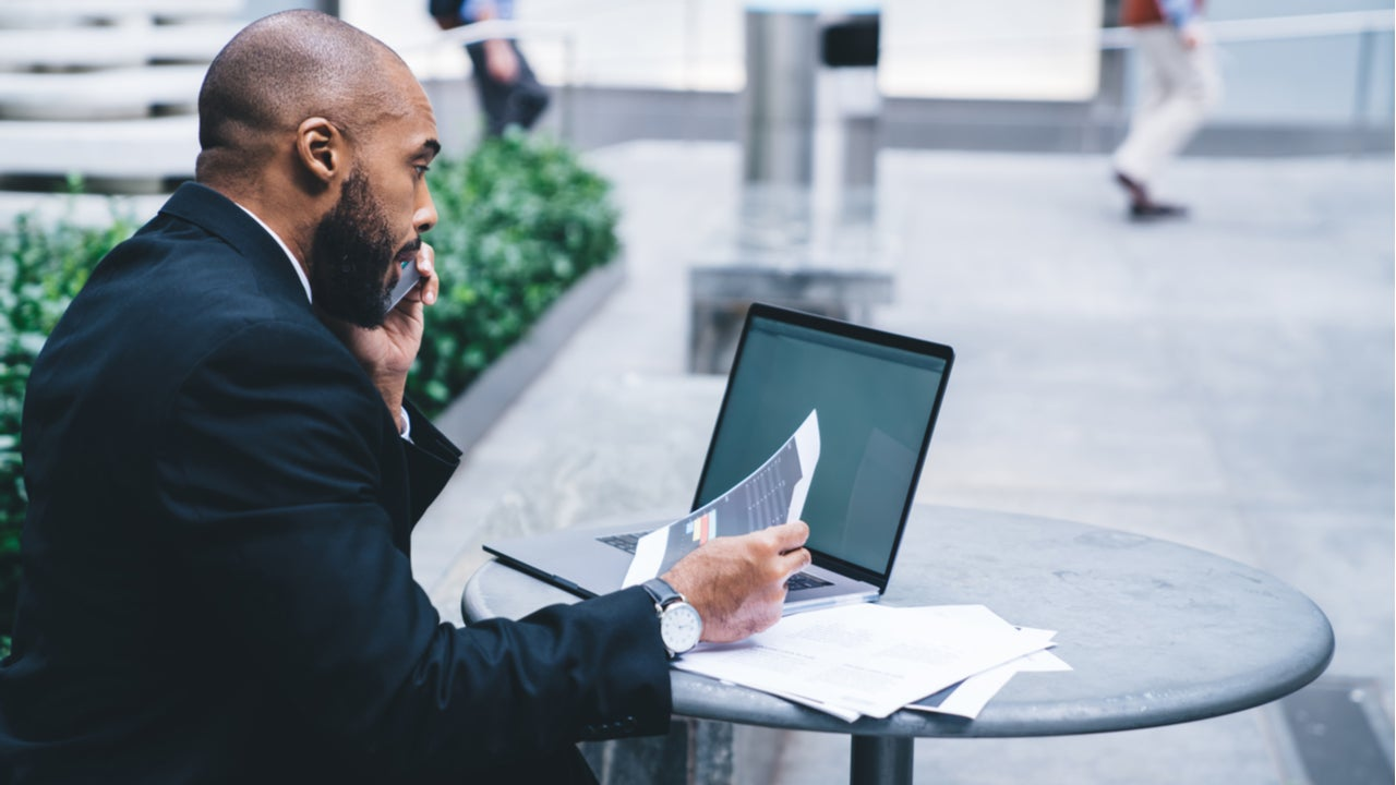 Black man working on laptop in public place