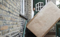Woman looking at package at entrance of house