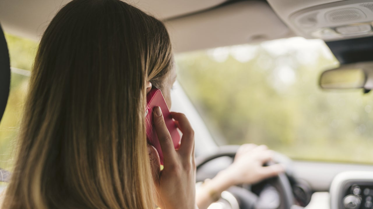 Rear view of young woman talking on the phone inside car