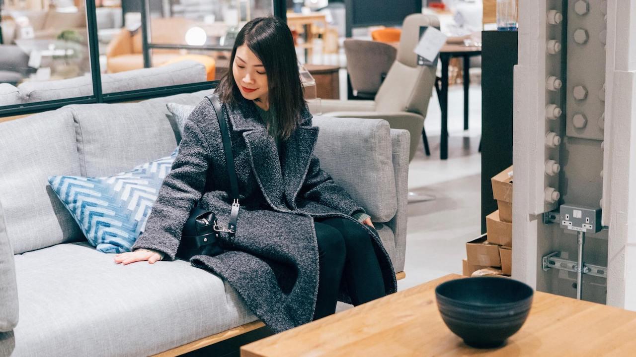 Young woman at furniture store choosing sofa
