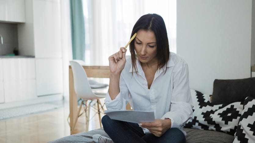 Worried woman reading document sitting at home