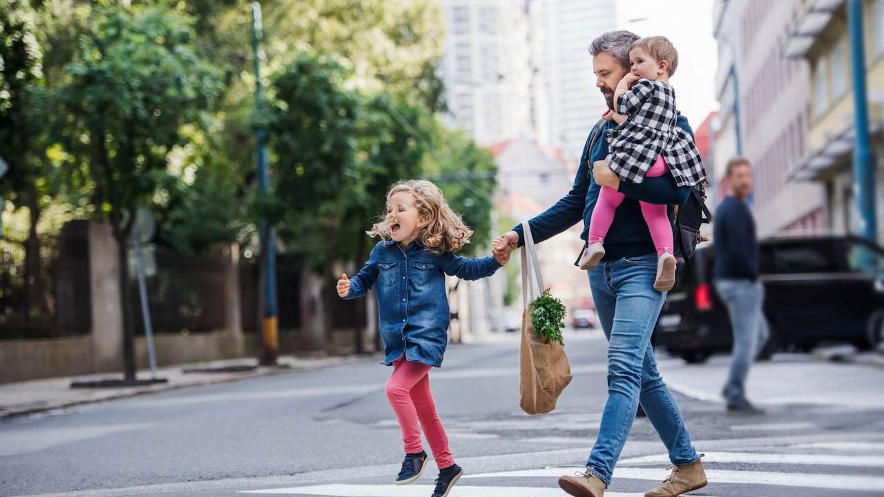 Father with small girls walking outdoors in city, crossing the road
